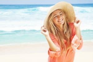 Women in hat on smiling on beach