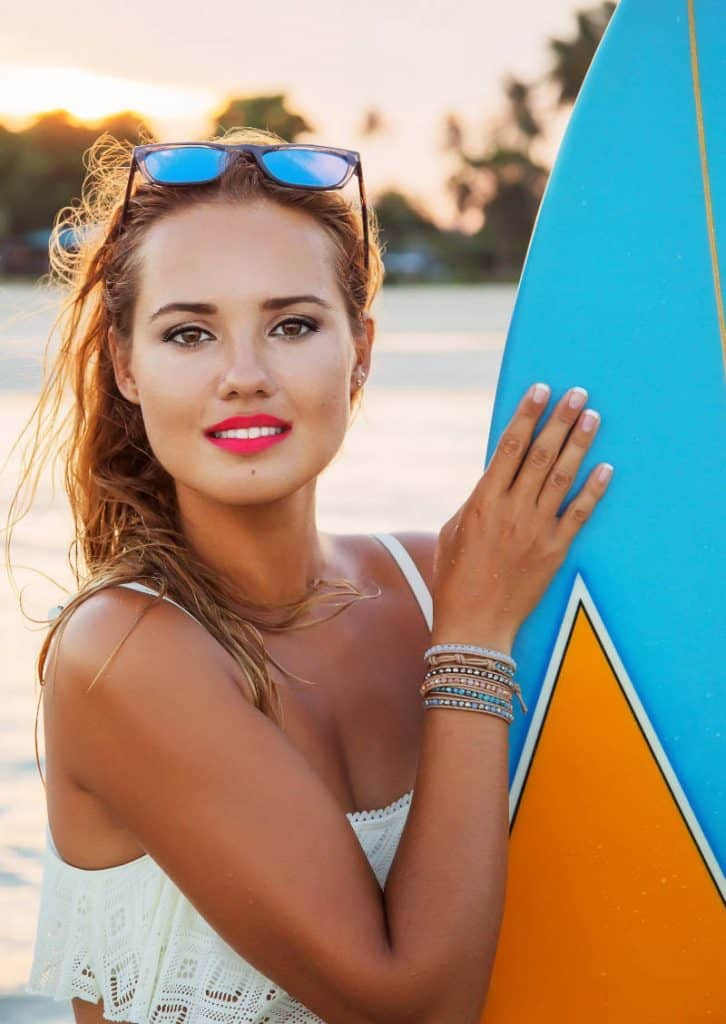 Smiling woman holding surfboard