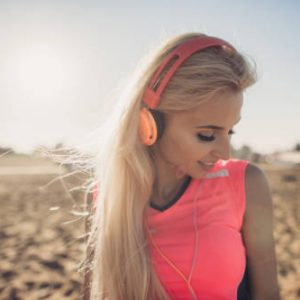 woman smiling and listening to music at beach