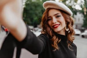 woman with beret smiling selfie