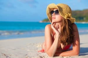 woman with hat laying on beach